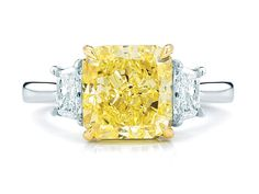 Beautiful three stone ring made of a large radiant cut intense yellow diamond with two tapered colorless diamonds on the sides