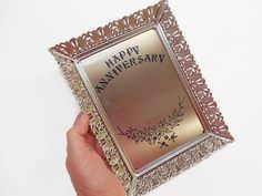 WAS $16.00.  What a wonderful gift for a silver wedding anniversary--or any anniversary, for that matter! Very pretty Hollywood Regency style frame can showcase your favorite photograph or small print, or you can display it as is, with the decorated metal insert shining prettily on its own. For a 5 x 7 photo or print; please note there is no glass, though you could add it if you wished by simply removing one of the cardboard shim pieces. I also notice there is no easel backing, but I will…