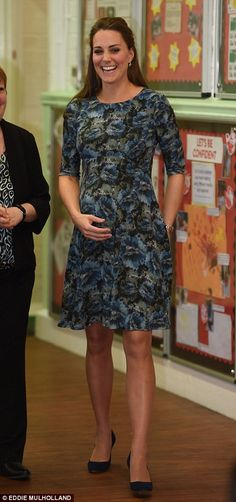 Dressed in a blue floral Seraphine maternity dress Kate, who's due in April, held her hand protectively over her baby bump