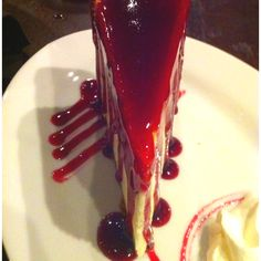 Tall NY Cheesecake with raspberry sauce and cream