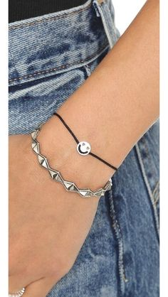 A smiley face charm with heart-shaped eyes slides along the woven cord of this Ruifier bracelet. Petite aglets tip the cord. Adjustable length.