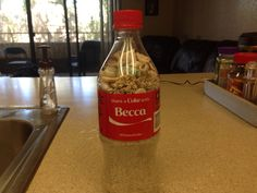 Coke bottle with Becca's name filled with sand and shells.