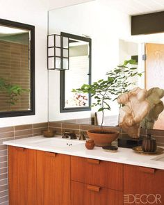 The countertop is CaesarStone, the sink fittings are by Waterworks, and the bronze-and-glass sconce is custom made.