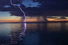 Surreal lightning over a calm ocean.