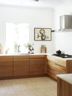 Wood face drawers/cabinets, white counters. White walls.