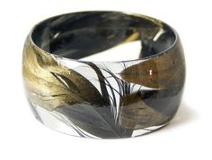 This wide slip on style bangle is made with real black and gold Feathers embedded into resin and shaped into this one of a kind bracelet.