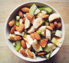 two bananas, two kiwis and a handful of almonds over greek yogurt