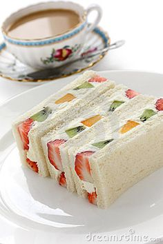 Sandwich with fresh fruits and cream filling and a cup of milk tea