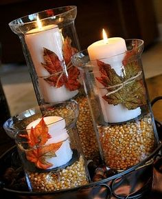 Thanksgiving or Fall Season Decorations, simple candle holders filled with corn, a silk leaf, and a candle, make it even nicer by sitting them in a shallow plate, bowl or basket of unshelled nuts.