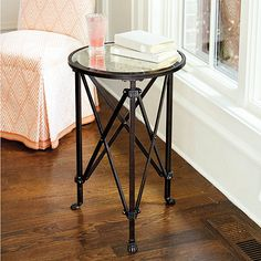 A stylish update on the classic French gueridon, this mirrored side table is just the right size for parking a drink beside your favorite chair. Its beveled antiqued mirror top is supported by three metal legs strengthened with X stretchers.Olivia Mirrored Side Table features: Dark antique brass with silver undertonesClaw feetRibbed collar details