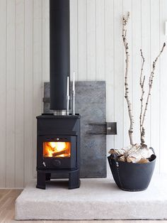 wood stove on stone platform - desiretoinspire.net - Carina Olander