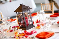 Centerpiece idea - rose petals, lantern with tea lights [IKEA has them on the cheap].