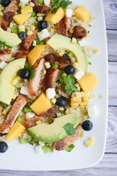 Blackened Chicken and Quinoa Salad - grilled chicken on top of quinoa tossed with a cilantro lime dressing! Plus avocado, mango, blueberries, grilled corn, and feta cheese!