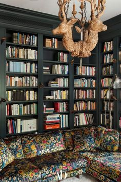 Painted in Studio Green by Farrow & Ball, the library reads as a magical forest of sorts, with a vintage chandelier in the form of three stags, a menagerie of carved birds gathered on the bookshelves, and a Neri&Hu sectional upholstered in exuberant botanical fabric. #library #libraries #homelibrary #vintage #chandelier #books #bookshelves #couch #sectional #upholstery #fabric #prints Outdoor Swimming Pool, Swimming Pools, Glass Garage Door, Scenic Wallpaper, Neri And Hu, Beautiful Library, Studio Green, Side Porch, Magical Forest