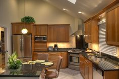 Natural Cherry Wood Kitchens- Stainless steel appliances, table style seating at lower table height, decorative wine bar area, full height backsplash behind the stove, natural cherry cabinets, granite countertops