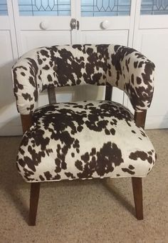 1950's chair recovered in faux cowhide. I added pleats and buttons to the back to update the look.