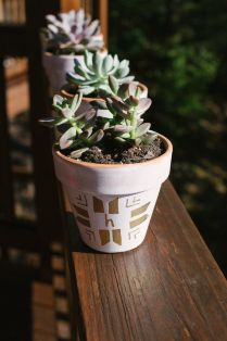 decorate this terra-cotta pot with white spray paint, metallic sharpie paint pens, and a whole lotta love. succulents not included, green thumb not required.