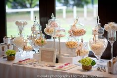 A decadent lolly buffet in tones of white and beige. Tall glass containers were filled with sweet treats.