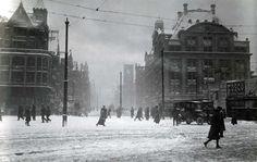 Amsterdam in de winter/sfeerbeeld. Sneeuw in Amsterdam. Voetgangers in de sneeuw op de Dam. Rechts het gebouw van De Bijenkorf en op de achtergrond de toren van de Beurs van Berlage. Op het reclamebord een affiche van Fosco, een heerlijke chocolade drank. Foto 1916.