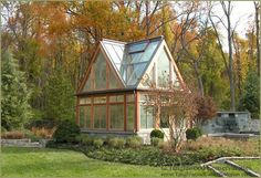 A Modern-styled Custom Greenhouse in Utah.  This elegant backyard greenhouse has a steeply pitched, copper roof and trim made from simple cedar boards that match the main house.