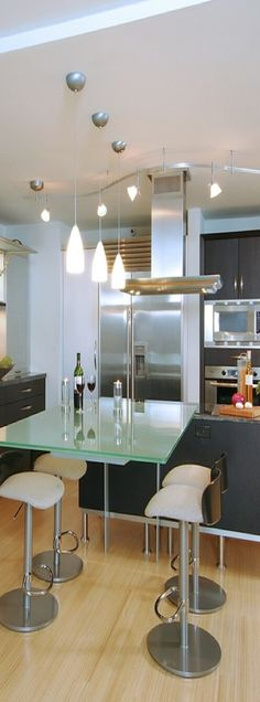 love the pale wood flooring, the green glass table top, the bar stools, the black cabinets and everything else white.
