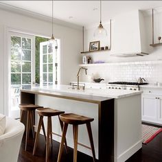 White kitchen with a rustic touch by @kindredcreativestudio  Love the wooden table extension of the white marbled top island.