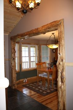 Really like the use of natural logs as trim to mark the doorway between rooms. If there are different types of wood (ash, cherry, etc.), prefer that the natural wood elements complement one another. In this image, there's too much going on with the dining room trim, chairs, floor, and ceiling all apparently in different finishes.