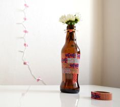 """A brown glass bottle turned into a lovely vase with a simple masking tape (washi tape - paper tape - マスキングテープ、ペーパーテープ) This tape includes japanese patterns. It is produced as a special serial related to the Japanese culture under the name of """"Mt.Fuji - Fujisan"""""""