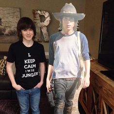 Chandler Riggs wearing a League Of Legends shirt while standing next to a cutout of his character, Carl Grimes from The Walking Dead