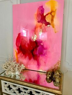 This one of a kind large abstract artwork is textured with a mixture of acrylic paints, recycled glass, and resin coating to create a truly unique and serene abstract original. The painting has a glass coat layer of epoxy resin to add a thick high gloss sheen to piece. Looks beautiful in natural light!!  The abstract ink pattern include shades of gold, red, pink, peach, iridescent glitter, and touches of gold leaf.  This is a signed original gallery wrapped heavy duty canvas that is 1 deep…