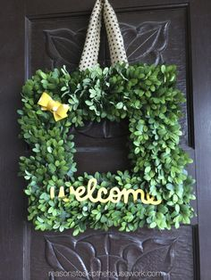 A welcome sign painted in yellow adds cheer to our English Boxwood Wreath. Via @Reasons To Skip The Housework