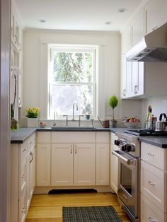"Classy City Kitchen -- a small galley kitchen opens up to the Dining Room in a 19th century Row House""--Dark countertop, cabinets and wall same color to make space appear larger."
