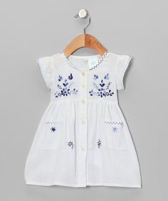 Handmade in the valleys of Ecuador, this sweet frock features flowers that are hand-stitched with variegated thread, making each blossom one of a kind.