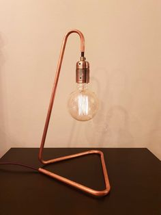 Get yours today! Crafted from a single length of copper with a natural finish, this elegant lamp with a dimmable exposed Edison bulb casts a warm light and creates a cosy atmosphere in any room. Copper Lamps, Copper Lighting, Sconce Lighting, Copper Table Lamp, Pipe Lighting, Copper Floor Lamp, Lighting Ideas, Table Lamps For Bedroom, Diy Table Lamps