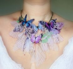 Necklace | Derya Aksoy.  She projects real photos of butterflies, moths and dragonflies onto crystal organza before delicately snipping and weaving with feathers, jewels and beads to make her pieces.