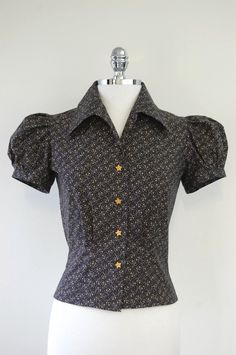 The early 40's inspired Nicolai blouse has a dart in each shoulder, six  flattering tucks at the waist and huge too-good-to-be-true puffed sleeves  that are gathered at the shoulders and the armbands. The crisp 1940's  collar will look simply amazing under your jumper or overalls! The print is  nautical stars and anchors on a Navy blue background. The blouse is  finished with golden yellow star shaped buttons.