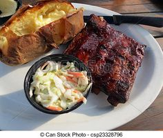 Barbequed spareribs served with a baked potato and coleslaw, on a picnic table out on the patio.