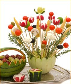 """This would be an impressive addition to the appetizer buffet for everything from parties & showers to Mother's Day brunch! Here's another design that features skewered veggies spraying from a melon """"basket"""" garnished with thyme Edible Centerpieces, Edible Bouquets, Edible Arrangements, Veggie Snacks, Veggie Tray, Edible Crafts, Edible Art, Fruit And Veg, Fruits And Veggies"""