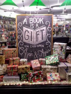 """A books is a gift you can open again and again"" Christmas bookstore window display."