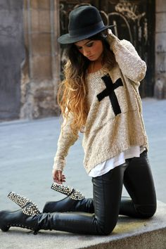 Woman wearing black leather pants, white sweater with black cross and black studded heels