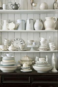 Wide planks of white beadboard make a charming backdrop for a collection of white china, creating the perfect fusion of rustic delicacy. The china and enamelware in this kitchen were collected during the family's travels to Europe—as well as visits to a few all-American garage sales.