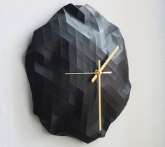 Faceted wall clocks are individually cast in black resin and are formed in a flexible mould which is manipulated by hand for each piece to give every clock a unique shape, so no two are the same.