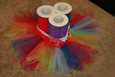 Get a roll of 6 inch wide tulle, cut into 10 inch pieces, use a .50 crochet style head band, I used a crochet hook to loop the tulle through the head band in two rows. For my rainbow colors I also used .50 roll of ribbon for the yellow, they didn't carry yellow rolls of tulle. TUTU for a 1 year old. <3  Total cost... (If you did 1 color) $4.50
