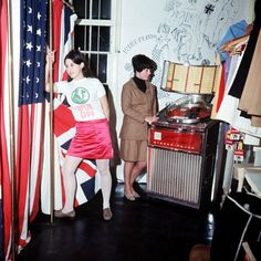 Inside Pauline Fordham's boutique on Ganton Street, near Carnaby Street. Customer Jackie Binder is in a 'with it' blouse and skirt standing beside a dressing room decorated with the Union Jack and the Stars and Stripes. In the background, Jacqueline Ball plays the juke box.