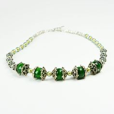 You'll look sharp in this baroque silver and green beaded necklace. Or give it to a woman who loves ornate detail. Either way, wearing this richly adorned necklace with echoes of Morocco is sure to capture attention. This 15 1/2-inch necklace is slightly longer than choker length, draping to the collar bone. It is composed of five swirled dark green 14mm German acrylic beads framed by silver finish bead caps. The strand is completed by two dozen 6mm iridescent Swarovski crystal pearl...