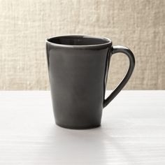 Shop Dark Grey Stoneware Coffe Mug.  Our most coveted casual dinnerware collection recalls the warm hospitality of Portugal's quaint seaside cafes.  Glazed dark grey, each free-form stoneware coffee mug is hand-antiqued at the rim by Portuguese artisans.