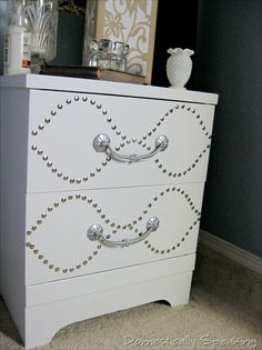 """Gotta little bling with only 1 buck! Using thumb tacks from Dollar Tree.  You trace a  pattern w/pencil & either drill a 1/4"""" hole or snip off the pin & glue on..I like antique brass or French natural myself w/ a different color chest."""