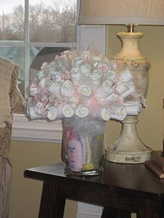 Diaper rose bouquet, instead of diaper cake  The diapers are rolled around wooden skewers and secured with clear rubber bands, and then pushed into a foam ball which is hidden and wedged into the vase. Accent with tulle. Isn't it pretty?