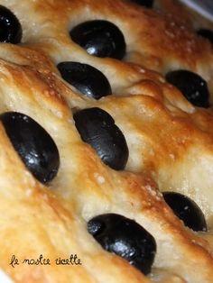 FOCACCIA CON OLIVE NERE 640 gr di farina 0-320 ml di acqua-2 cucchiai di olio extra vergine di oliva-1 cucchiaio di fiocchi di patate-1 cucchiaino di sale-1 cucchiaino di zucchero-Mezza bustina di lievito di birra Mastrofornaio-100 gr di olive nere snocciolate-Olio extra vergine di oliva q.b.-Sale q.b.