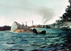 The capsized hull of USS Oklahoma BB-37 and damaged USS Maryland BB-46. December 7, 1941; Pearl Harbor, Hawaii